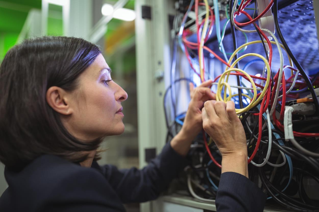 photo of woman fixing coloured wires in a network cabinet