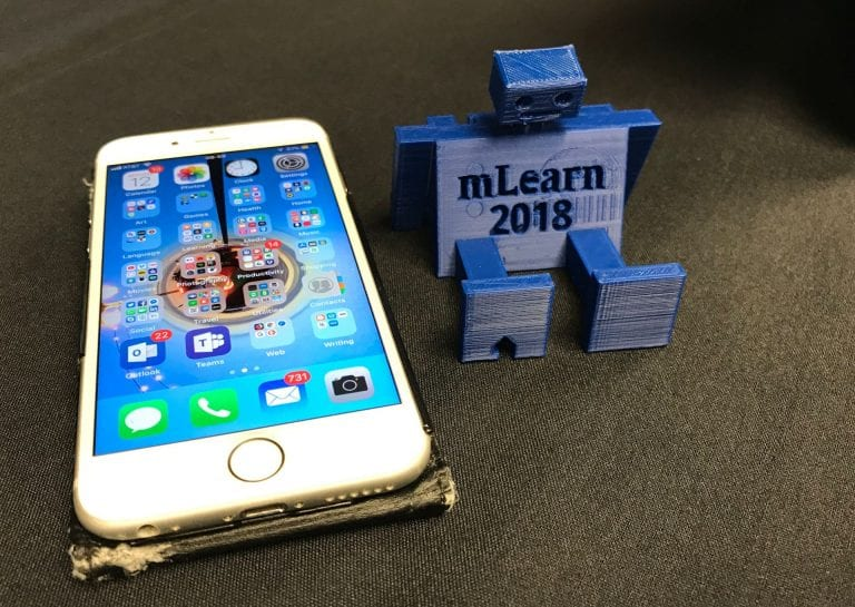 Photograph of a 3D-printed robot phone holder, plus iPhone 6s