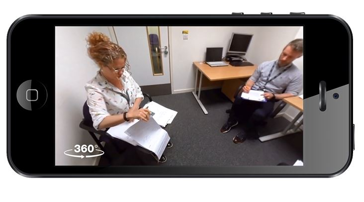 Colour image of a man and a woman sitting in a room undertaking a consultation as seen on a mobile phone