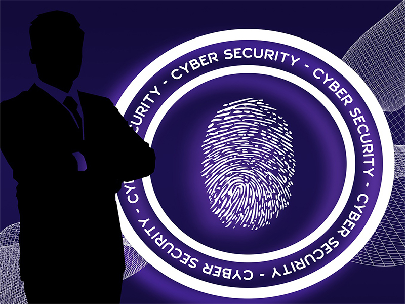 shadow of a man stood in front of  large round with cyber security around a thumb print