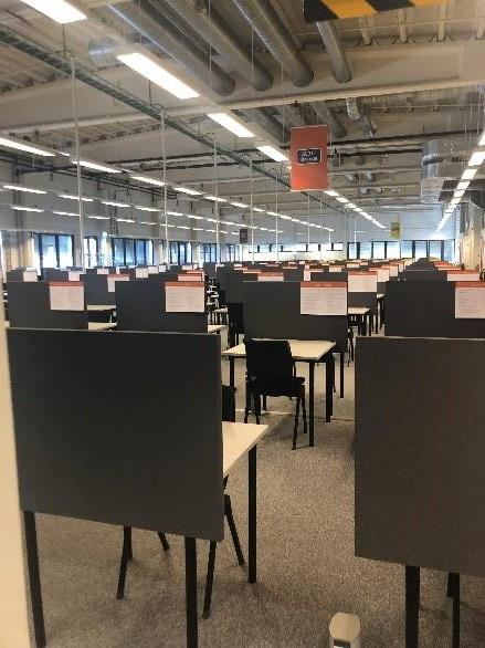 Colour photograph of the interior of the Exam Factory showing rows of screened desks with chairs with notes on the desk screens