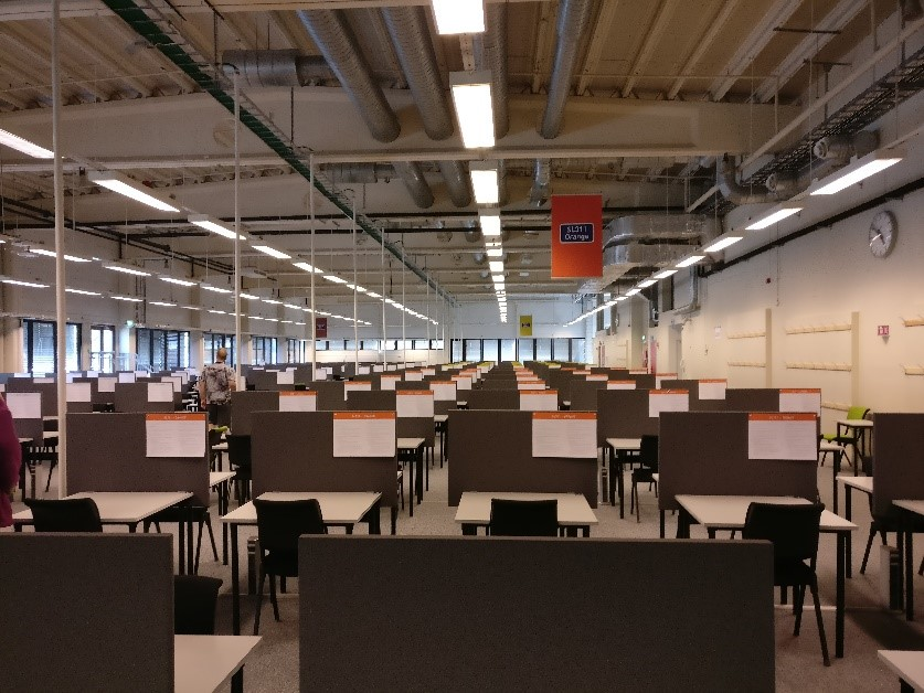 Photograph of NTNU Eksamen (Exam) building interior with long rows of desks and chairs set up for exams