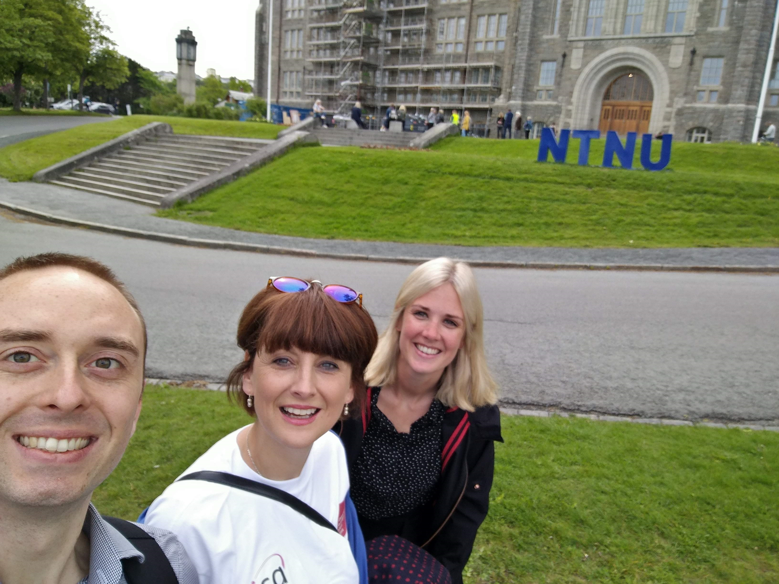 Colour photograph of bursary winners Sam Harrow, Elizabeth Griffiths and Samantha Chester in front of an NTNU building