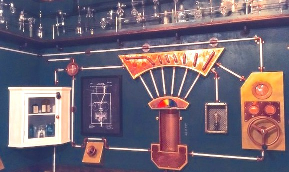 Image from Room Escape Artist's review of the Edison Escape Room in SF showing pipes, turning handles and a cupboard with bottles